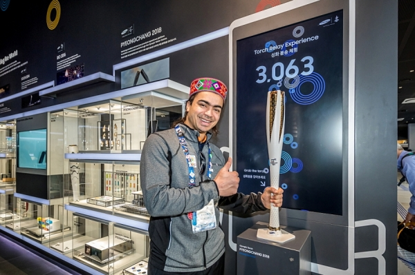 "An example of ""Do What You Can't,"" six-time Olympian from India, Shiva Keshavan stops to hold the Olympic torch as he learns about Samsung's 20-year heritage as a Worldwide Partner in the Wireless Communications Equipment category while visiting the Samsung Olympic Showcase in Gangneung Olympic Park in South Korea during the Olympic Winter Games PyeongChang 2018."