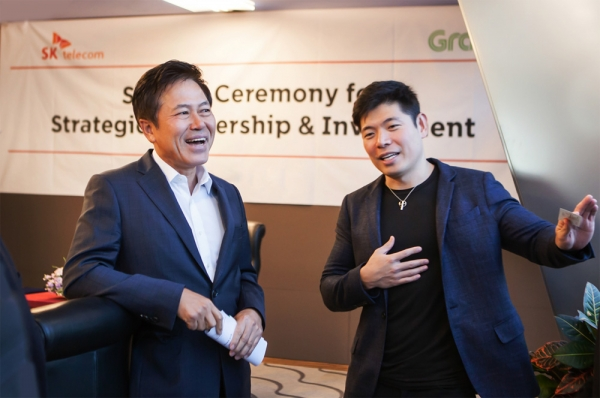 "SK Telecom CEO Park Jung-ho (left) and CEO Anthony Tan of Grapp are holding talks with each other after signing a JV ""Grap Geo Holdings"" agreement on January 30 at SK Telecom's headquarters in Eulji-ro, Jung-gu, Seoul."