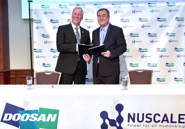 Na Ki-yong, head of Doosan Heavy's nuclear power center (right) and John L. Hopkins, CEO of Nuscale Power, are taking a photo while holding up the agreement after signing the MOU on April 29(local time) at the signing of a memorandum of understanding to cooperate on the Small Modular Reactor project of NuScale Power.