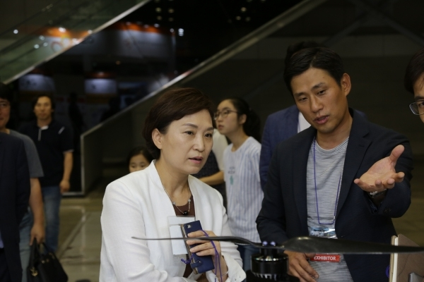 "Asoa CEO Kim Hyun-soo gives product descriptions to Land, Infrastructure and Transport Minister Kim Hyun-mee at the ""LoboUniverse & K Drone VR Summit"" event held in June last year"