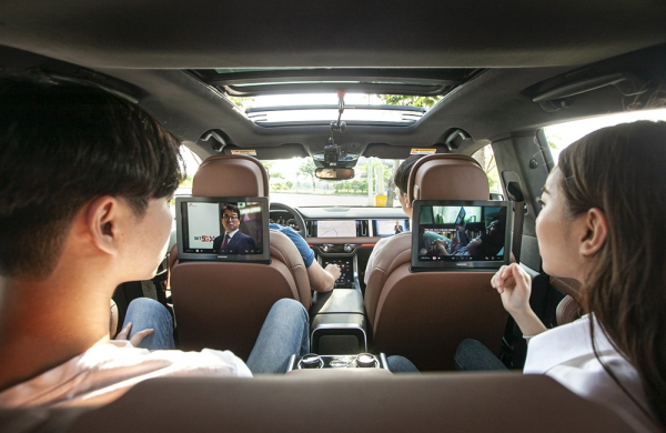 Vehicle occupants are watching a different 5G-ATSC3.0 based TV commercial on the screen in the vehicle.