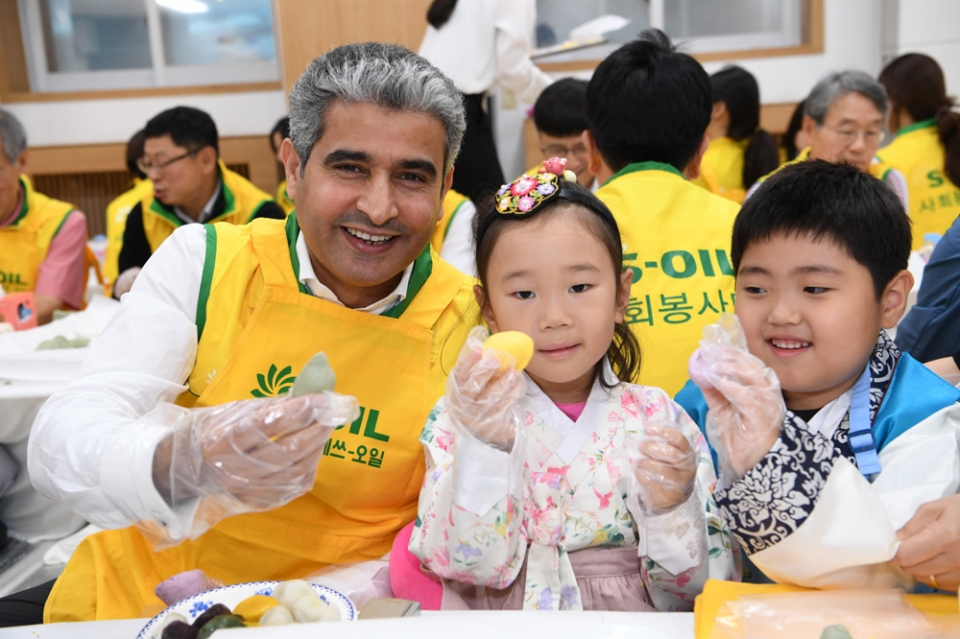 S-OIL CEO Hussain Al-Qahtani (far left) poses for the camera with children with  songpyeon that he himself made. (Courtesy of S-OIL)