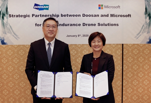 Doosan Mobility Innovation CEO Lee Doo-soon (left) and Korea Microsoft Vice President Woo Mi-young sign an agreement to develop a hydrogen fuel cell drone solution in Las Vegas on Jan. 8 (local time).