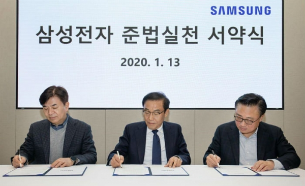 Samsung Electronics Vice Chairman Kim Ki-nam (center) signs the pledge at the Samsung Electronics Compliance Implementation Ceremony on Jan. 13./ Courtesy of Samsung Electronics
